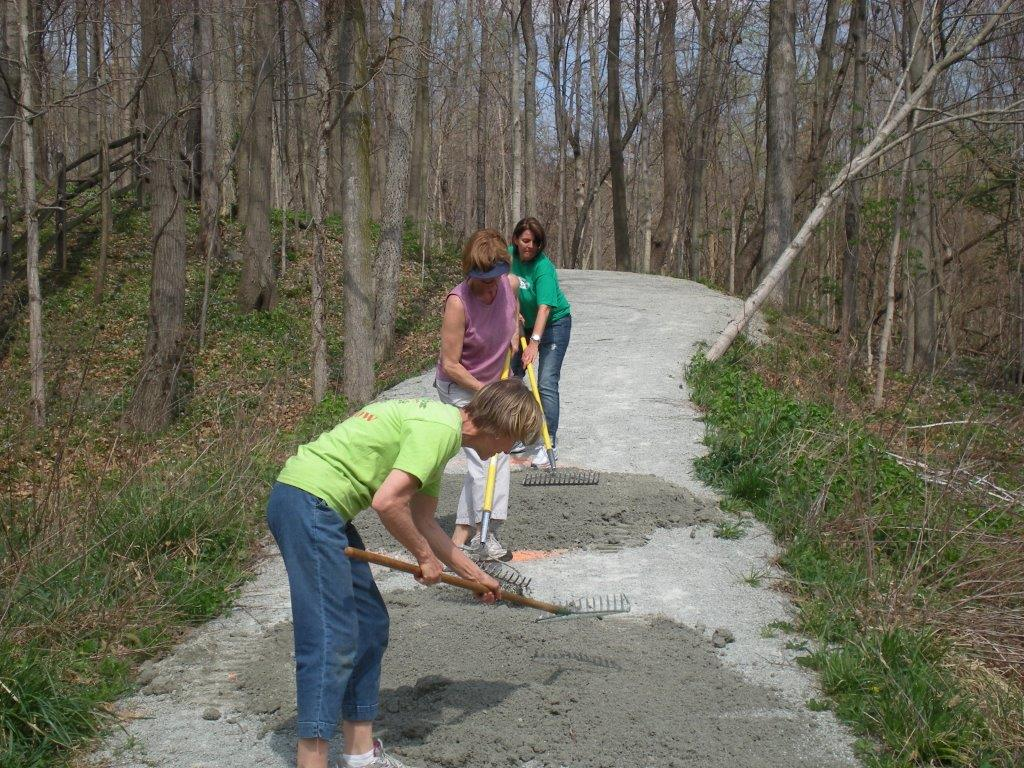 Three volunteers smoothing out trail for maintenance