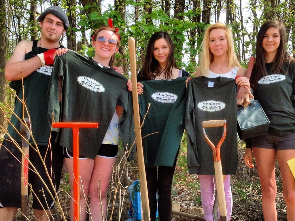 Five young adults standing with T-shirts for volunteering to plant